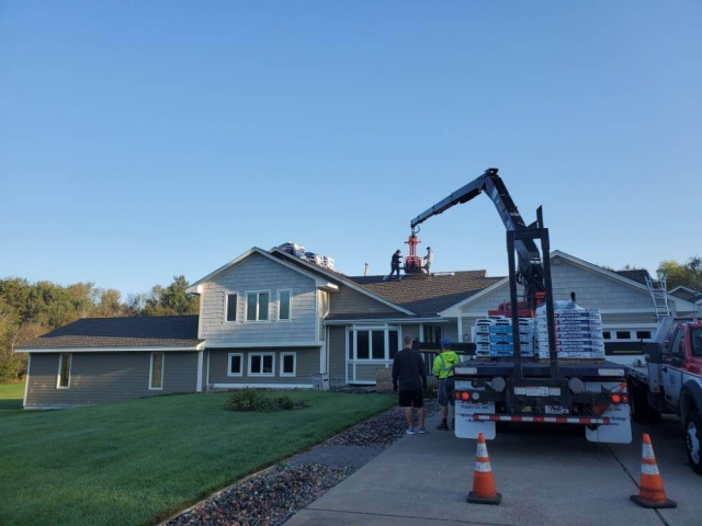 Roofing materials being delivered to home.