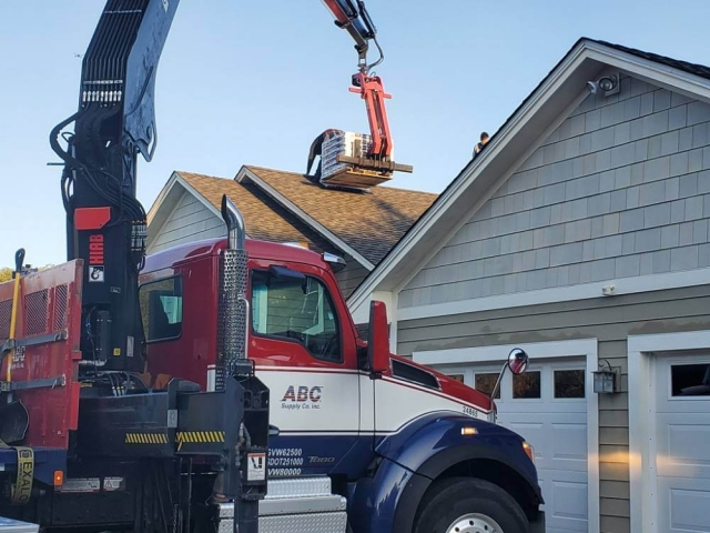 Crane truck lifting roofing materials onto home.